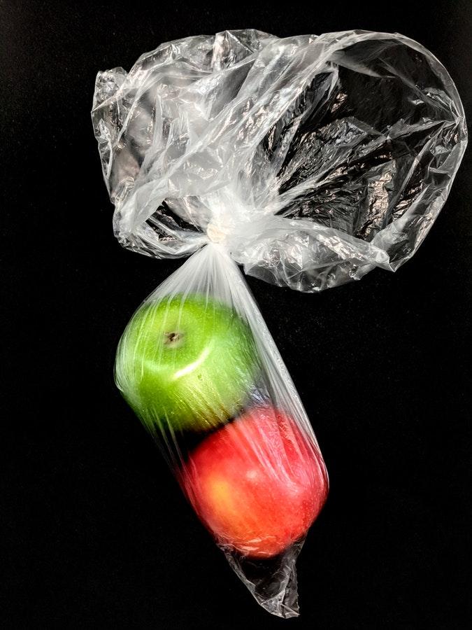 Manzanas envueltas en una bolsa de plástico.